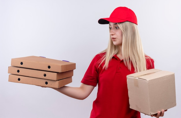 Ragazza giovane di consegna di pensiero che indossa la maglietta rossa e la scatola della tenuta del cappuccio che esamina la scatola della pizza sulla sua mano sulla parete bianca isolata Foto Gratuite