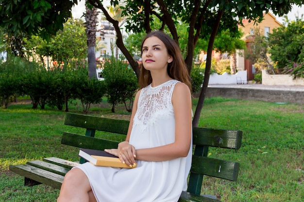 Thinking female student is sitting and holding a book in the park Premium Photo