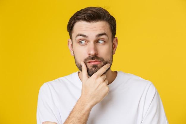 黄色に分離された思考の男。 copyspaceを見上げてカジュアルな若い物思いに沈んだ男のクローズアップの肖像画。白人男性モデル。 Premium写真