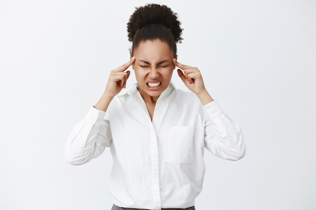 Pensare con tutta la potenza del cervello. ritratto di donna dall'aspetto serio concentrato intenso con la pelle scura in camicia da colletto bianco, serrando i denti e sollevando la tensione mentre cerca di concentrarsi e truccare il piano Foto Gratuite
