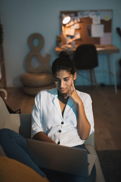 Thinking woman working on laptop from home Free Photo
