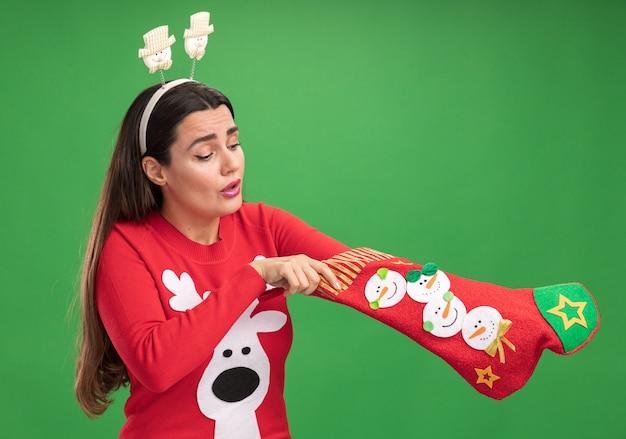 Думая молодая красивая девушка в рождественском свитере с рождественским обручем для волос, положив руку в рождественские носки на зеленом фоне Бесплатные Фотографии