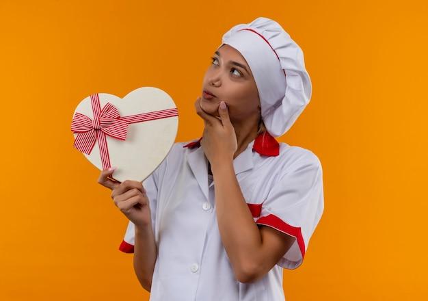 孤立したオレンジ色の背景のあごに彼女の手を置くハート型ボックスを保持しているシェフの制服を着ている若い料理人の女性を考える 無料写真