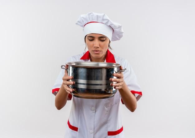 コピースペースのある鍋を持って見ているシェフの制服を着た若い女性料理人 無料写真