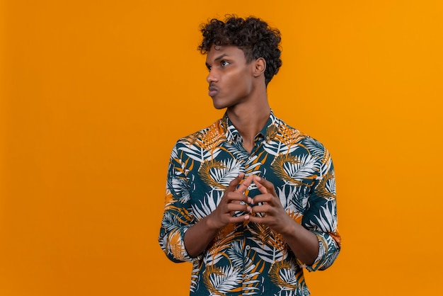 Thinking young handsome dark-skinned man with curly hair in leaves printed shirt holding hands together on an orange background Free Photo