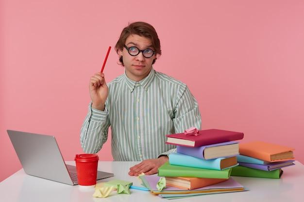 眼鏡をかけた若い男がテーブルのそばに座ってラップトップで作業し、見上げ、鉛筆を手に持って、ピンクの背景の上に孤立した難しい方程式を解こうとしています。 無料写真