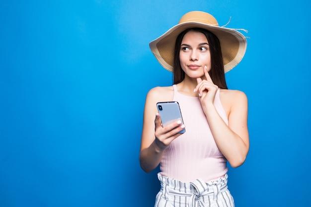 Думающая молодая женщина в соломенной шляпе с помощью мобильного телефона, изолированного над голубой стеной. Бесплатные Фотографии