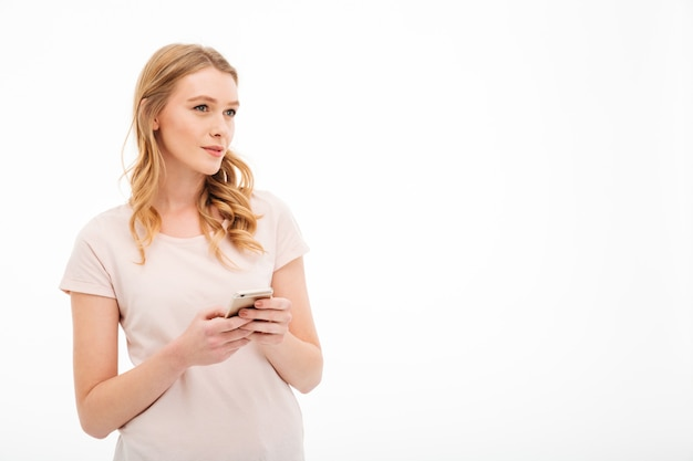 Thinking young woman using mobile phone. Free Photo