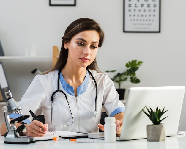 Thinkling female doctor looking on laptop Free Photo