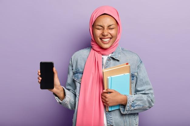 Это телефон, который вам нужен. радостная женщина с исламскими взглядами, носит традиционный хиджаб, показывает экран смартфона и смеется Бесплатные Фотографии