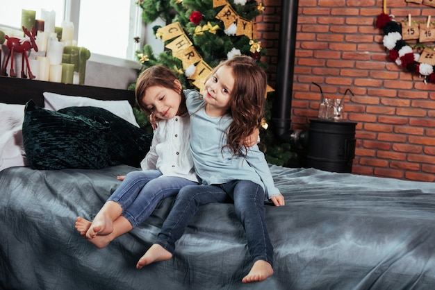 This is truly friendship. kids sits on the bed with decorative background. conception of new year Premium Photo