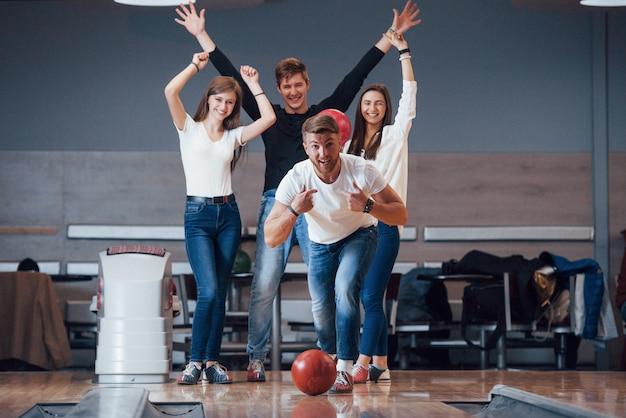 Questa è una vittoria. i giovani amici allegri si divertono al bowling durante i fine settimana Foto Gratuite