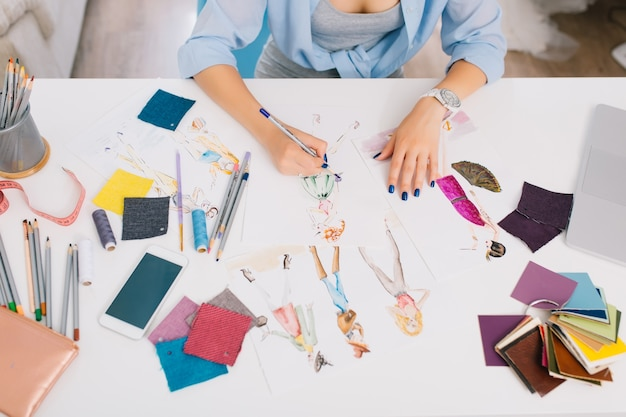 This picture describes the processes of designing clothes. there are hands of a girl drawing sketches on the table. there is creative mess with different stuff on the table. Free Photo