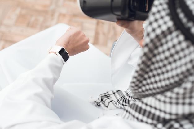 アラビア服thobeの男が彼の腕時計を見ています。 Premium写真
