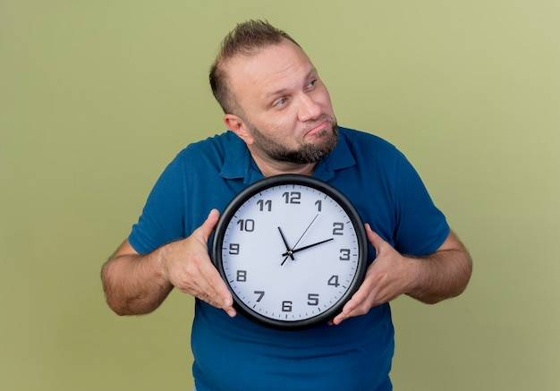Thoughtful adult slavic man holding clock looking at side Free Photo