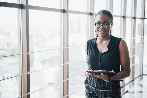 A thoughtful african american business woman wearing glasses holding documents Free Photo