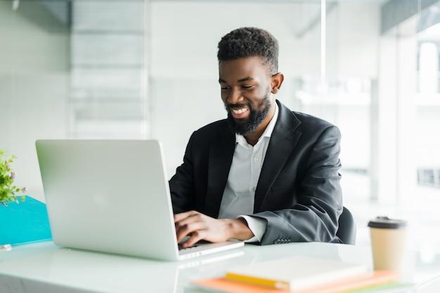 Uomo d'affari afroamericano premuroso che utilizza computer portatile, progetto di riflessione, strategia aziendale, dirigente perplesso dei dipendenti che esamina lo schermo del computer portatile, lettura della posta elettronica, presa della decisione all'ufficio Foto Gratuite
