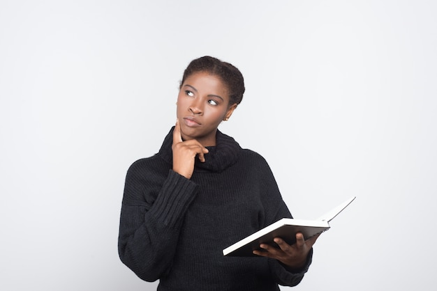 Thoughtful african american woman holding open notebook Free Photo