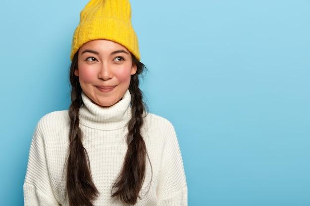 유쾌한 미소로 사려 깊은 매혹적인 젊은 아시아 여성, 파란색 배경 위에 절연 겨울 옷을 입은 두 개의 어두운 주름이 있으며 매력적인 태도를 표현합니다. 무료 사진