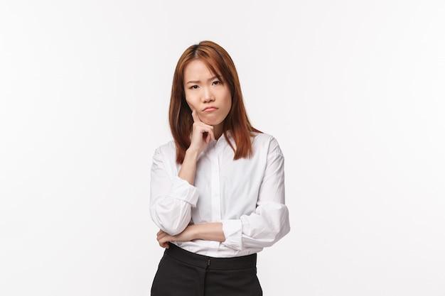 思慮深く、深刻な不機嫌そうな若いアジアの女性の思考、メイクアッププランに問題がある、片手で傾く Premium写真