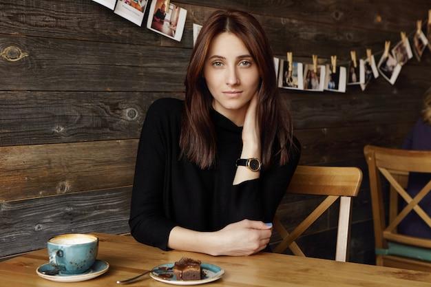 エレガントな黒のドレスと手首の時計を身に着けている思いやりのある美しいブルネットの女性は、コーヒーブレーク中にマグカップとデザートでカフェのテーブルに座って一人で素敵な時間を楽しみながら首に触れます 無料写真