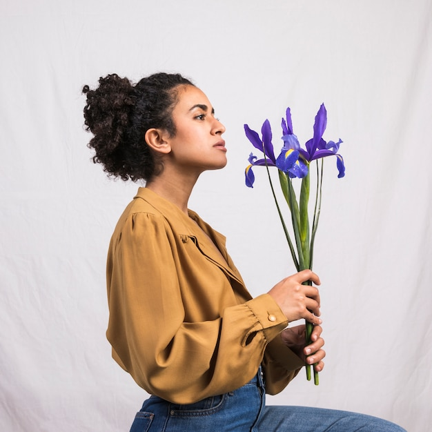 Thoughtful black woman holding blue flower Free Photo