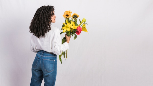 Thoughtful black woman holding flowers bouquet Free Photo