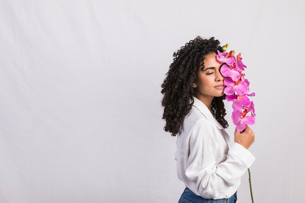 Thoughtful black woman with big pink flower Free Photo