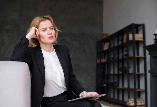 Thoughtful blond business woman in suit with tablet Free Photo