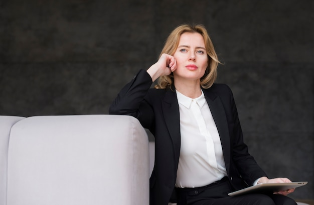 Thoughtful blond business woman with tablet Free Photo
