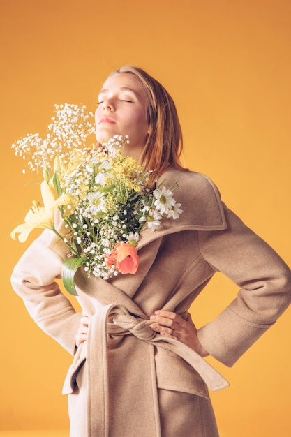 Thoughtful blond woman with flowers bouquet in coat Free Photo