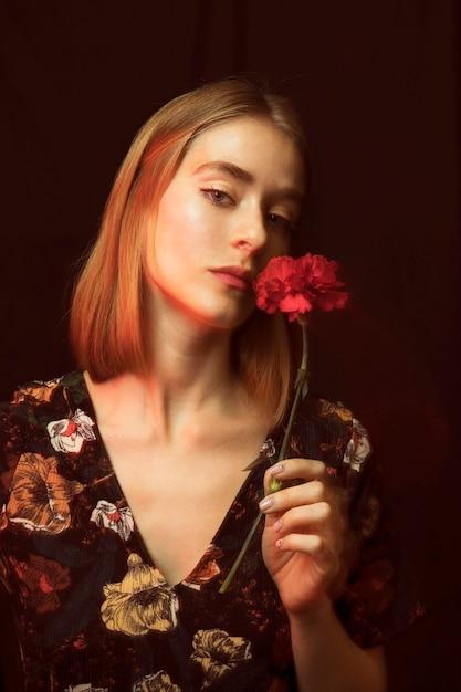 Задумчивая белокурая женщина с красной гвоздикой Бесплатные Фотографии