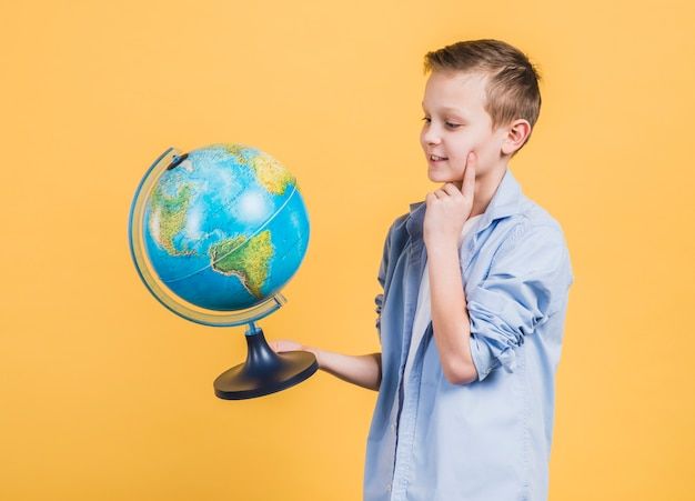 Thoughtful boy looking at hand globe standing against yellow background Free Photo
