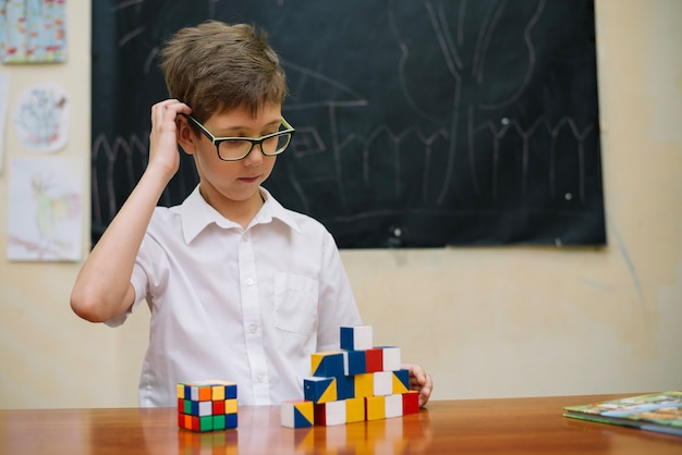 Thoughtful boy with puzzle toys Free Photo