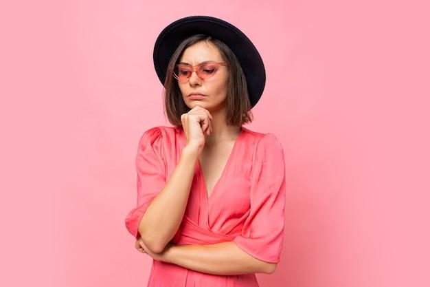 분홍색 벽에 포즈 세련 된 안경에 사려 깊은 갈색 머리 여자. 무료 사진