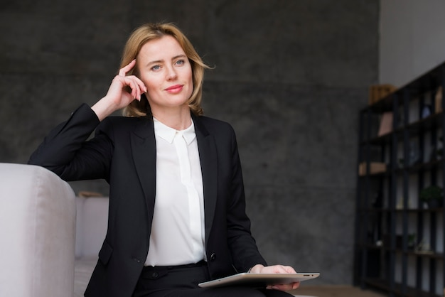 Thoughtful business woman sitting with tablet Free Photo