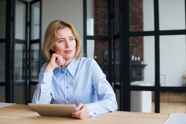 Thoughtful business woman using tablet at table Free Photo