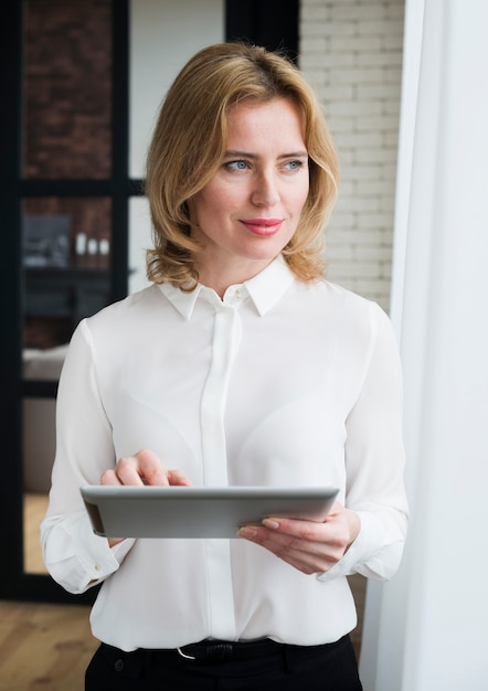 Thoughtful business woman using tablet Free Photo
