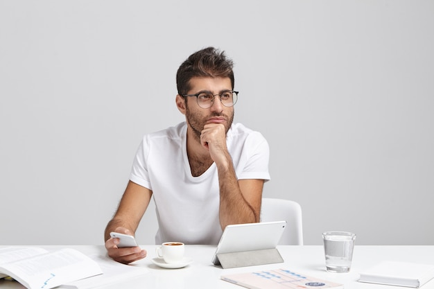 Thoughtful business worker tries to concentrate, holds mobile phone as waits for important call Free Photo
