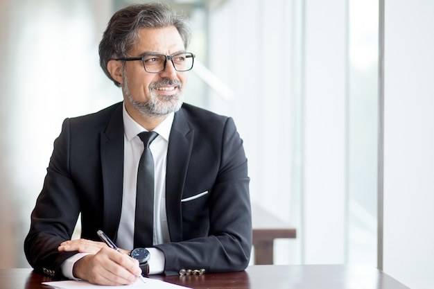 Thoughtful businessman in suit making notes Free Photo