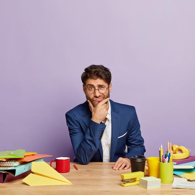 사무실 책상에 앉아 사려 깊은 사업가 무료 사진