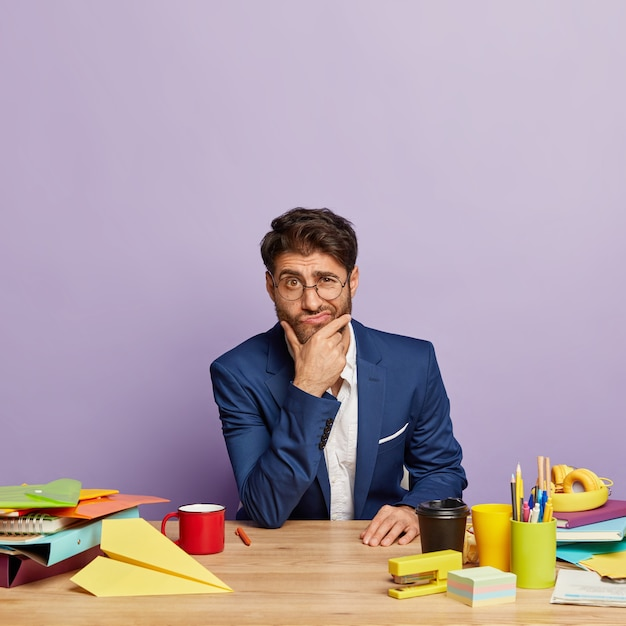 Thoughtful businessman sitting at the office desk Free Photo