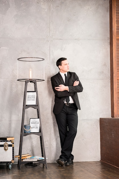 Thoughtful businessman with crossed arms looking away Free Photo