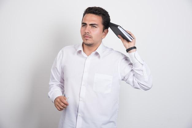 Uomo d'affari premuroso con il taccuino che sta su priorità bassa bianca. Foto Gratuite