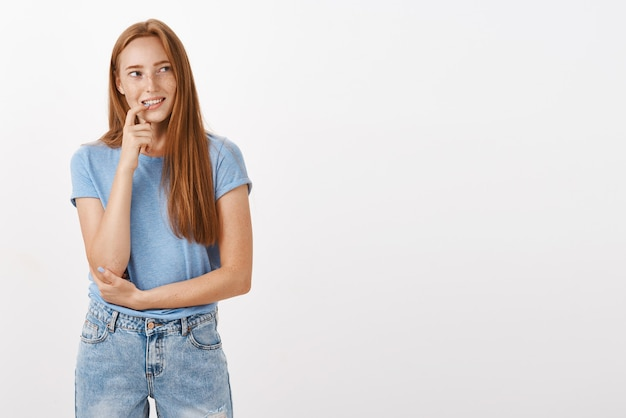 Thoughtful calm and joyful attractive redhead female with freckles biting finger gazing at upper right corner while thinking or remembering Free Photo