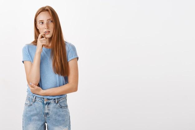 青いtシャツとジーンズをかむ指で思慮深く集中して好奇心が強い赤毛の女性 無料写真