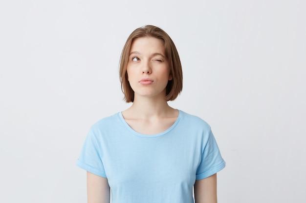 Задумчивая сосредоточенная молодая женщина в синей футболке с закрытыми глазами думает и пытается вспомнить ответы Бесплатные Фотографии
