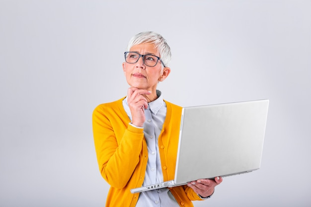 Thoughtful confused mature business woman concerned thinking about online problem looking at laptop, frustrated worried senior middle aged female reading bad email news, suffering from memory loss Premium Photo