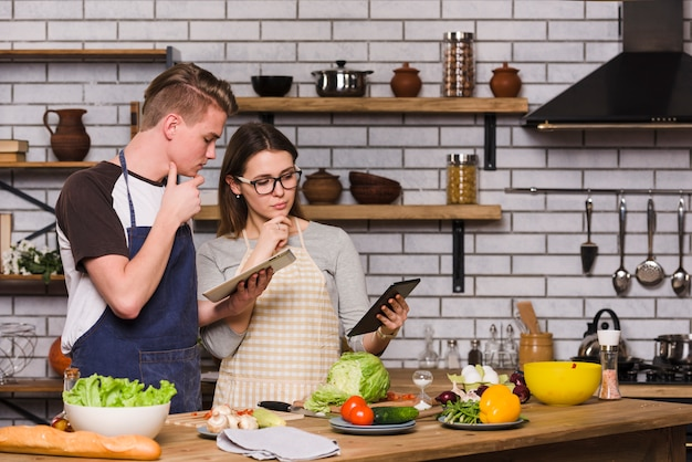 Thoughtful couple with tablets in kitchen Free Photo