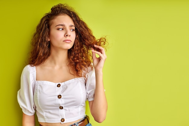 Thoughtful curly girl is looking at split ends of hair, examine it, want to cut out Premium Photo